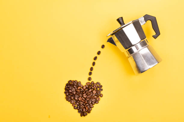Coffee maker and beans Coffee beans pouring from coffee maker into a heart shape on yellow background. Love coffee concept. Flat-lay, top view. coffee pot stock pictures, royalty-free photos & images