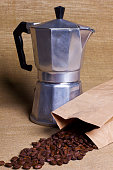 coffee maker on canvas table and paper bag with coffee grains