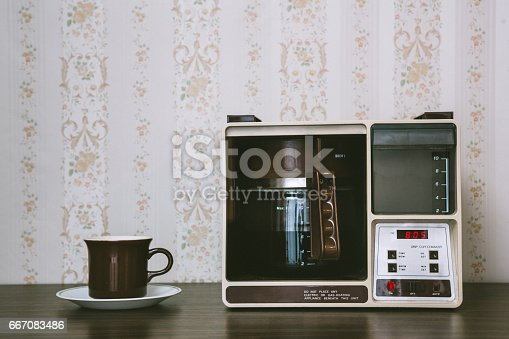 A vintage looking automatic coffee machine sits on the counter of a 1970's / 1980's style kitchen with floral wallpaper and a mug ready to be filled.  Brown and yellow color theme.   Horizontal with copy space.