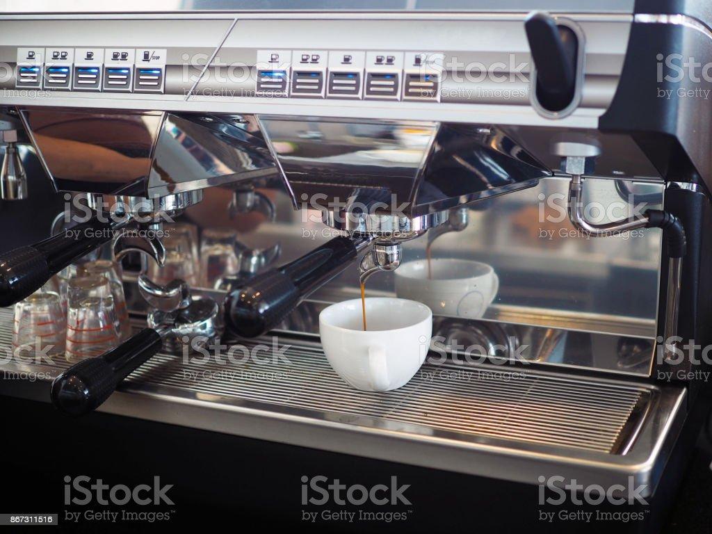 Máquina de café expresso em xícara branca de enchimento. - foto de acervo