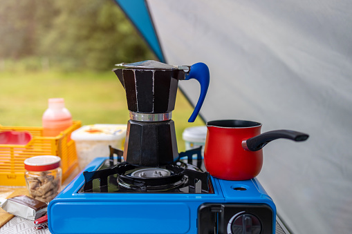 Coffee maker on a gas cooker outside a tent