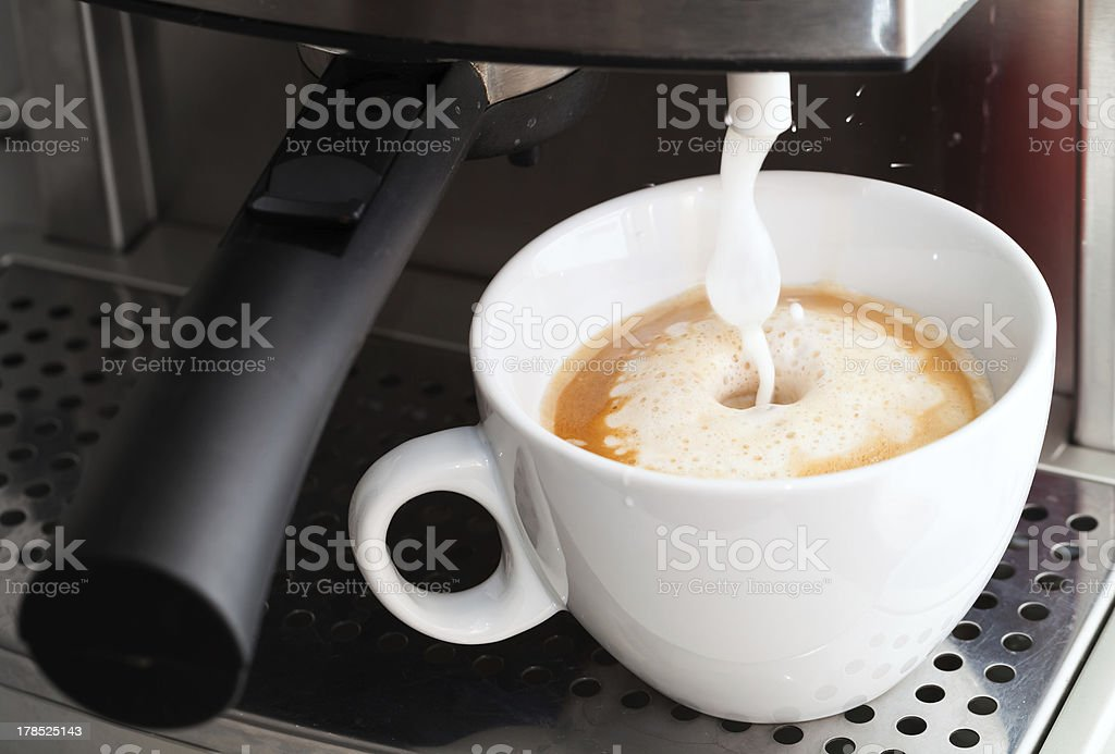 Coffee maker pouring hot milk foam royalty-free stock photo