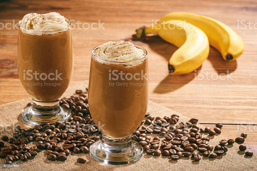 Coffee milk cocktails with banana on wooden background. stock photo