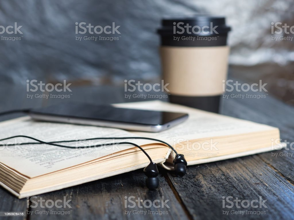 Caneca de café, fones de ouvido e um livro. O conceito de um audiolivro e uma moderna biblioteca eletrônica - foto de acervo