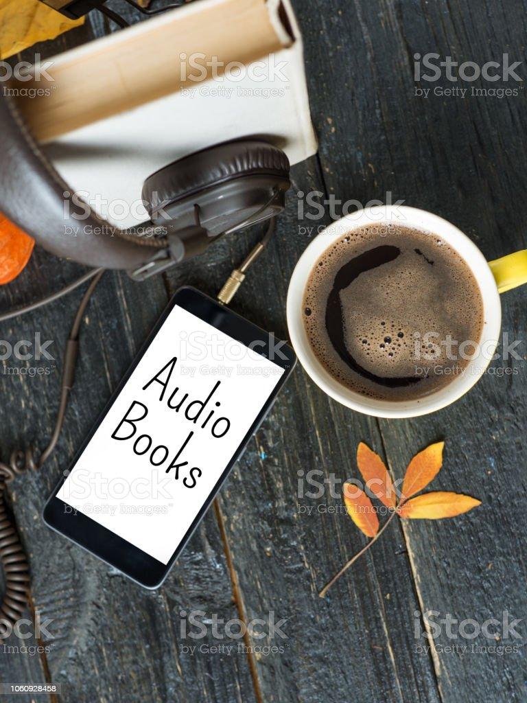 Caneca de café, fones de ouvido e livro sobre fundo escuro de madeira. Conceito de audiobook - foto de acervo