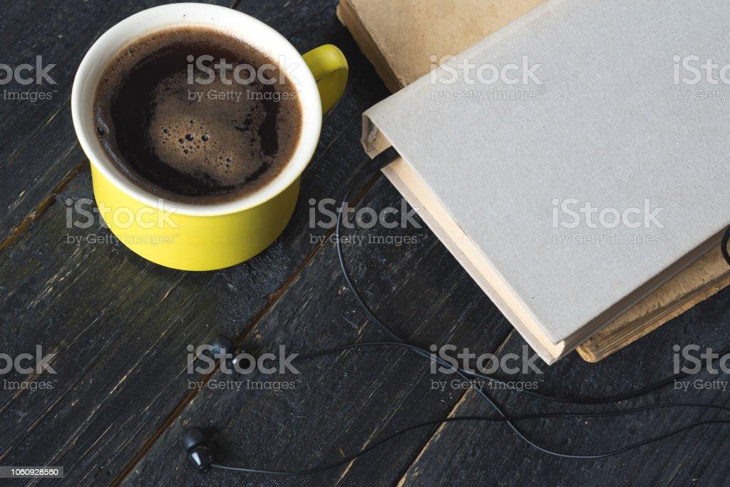 Caneca de café, fones de ouvido e livro sobre fundo escuro de madeira, conceito de audiobook - foto de acervo
