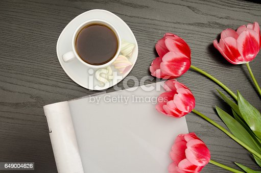 Coffee mug, marshmallow, clean sheet and pink tulips. Black table. top view