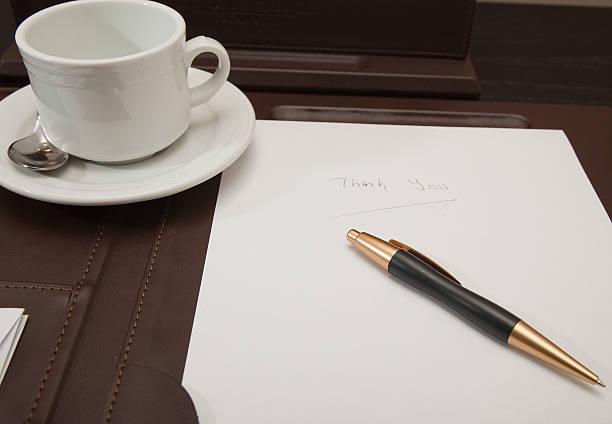 Coffee mug, notebook and  pen on desk pad