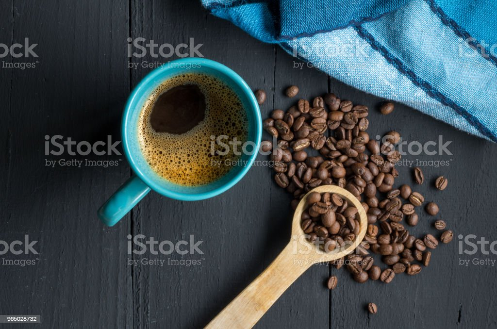 Coffee mug on rustic black wooden kitchen table with coffee beans and space for text royalty-free stock photo