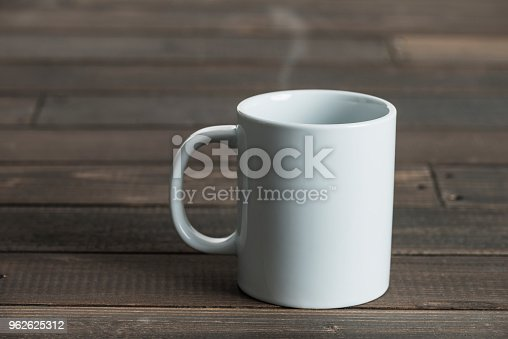 White coffee mug on wooden background.