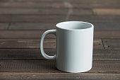 White coffee mug on wooden background.