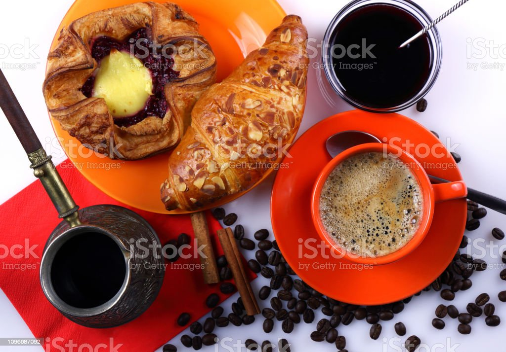 Still life with orange coffee cup, croissant, cheesecake, coffee...