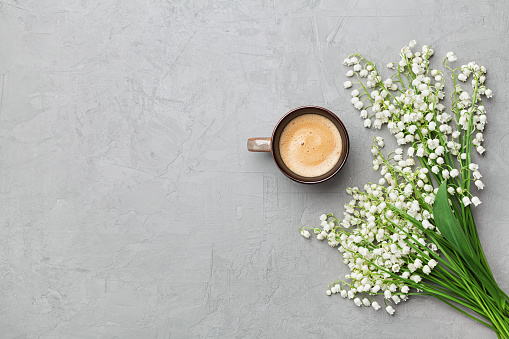 Coffee mug with bouquet of flowers lily of the valley on gray stone table top view in flat lay and minimalistic style. Beautiful morning breakfast.