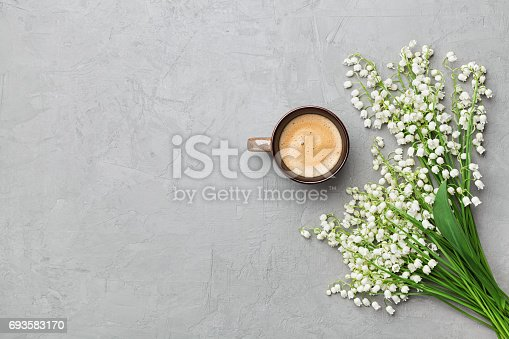 istock Coffee mug with bouquet of flowers lily of the valley on gray stone table top view. Flat lay. 693583170