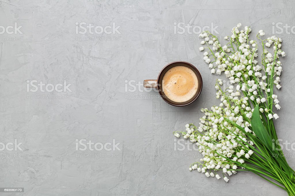 Coffee mug with bouquet of flowers lily of the valley on gray stone table top view. Flat lay. stock photo