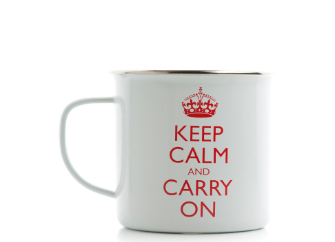 London, England-March 29, 2011.  White metal coffee mug with the famous British saying Keep Calm and Carry On written on it.  Mug is on a white background.