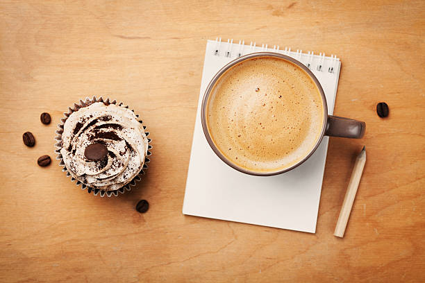 Coffee mug with cupcake, notebook and pencil on rustic table stock photo