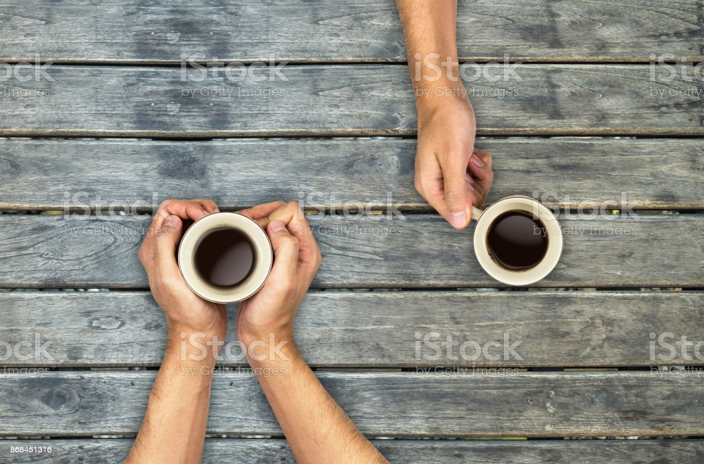 Coffee mugs hands holding on wood table, top view angle stock photo