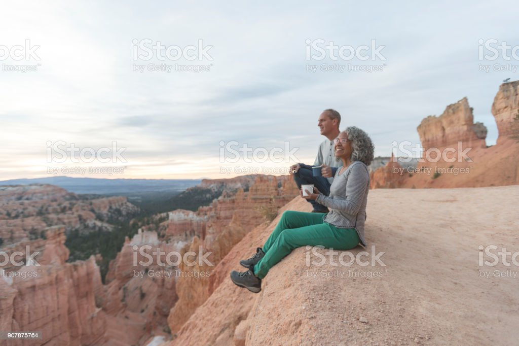 Coffee on a Cliff An older couple take a break from hiking to enjoy the view at Utah outlook overlooking a canyon. They are sitting on the cliff's edge and soaking in the scenery. The mountains and canyon are in front of them. Active Lifestyle Stock Photo