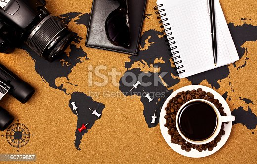 Cup of black coffee on a map with pins, camera, binoculars, passport, sunglasses, notepad and pen. Top view.