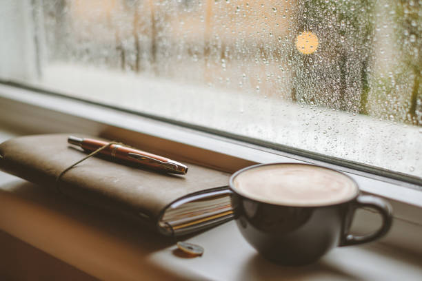 Coffee on a window sill in a rainy day. stock photo