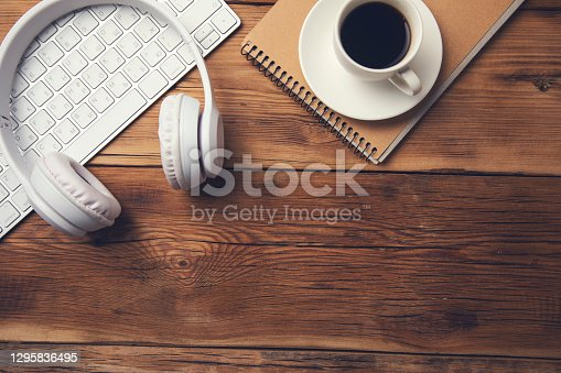 coffee on notepad with earphone and keyboard on table