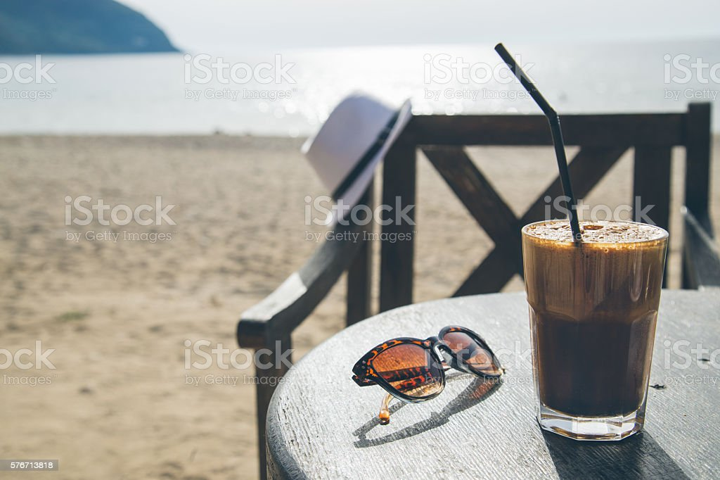 coffee on table over beach background stock photo