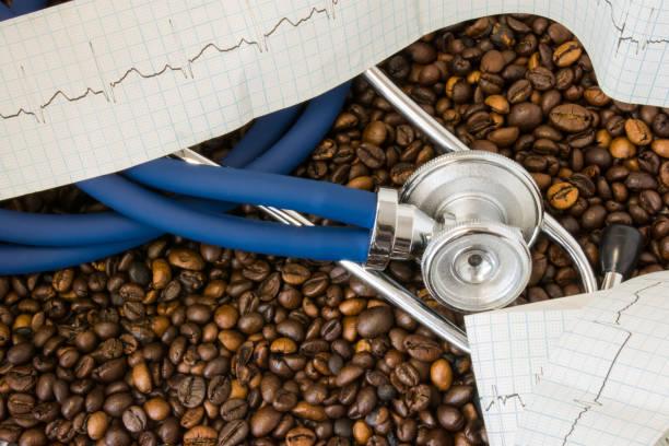 kaffe eller koffein och hjärtat arytmier (oregelbunden hjärtrytm). stetoskop och ekg tejp på bakgrund av kaffebönor. effekt och risk för att dricka kaffe eller koffein på hjärtarytmi utveckling - coffe with death bildbanksfoton och bilder