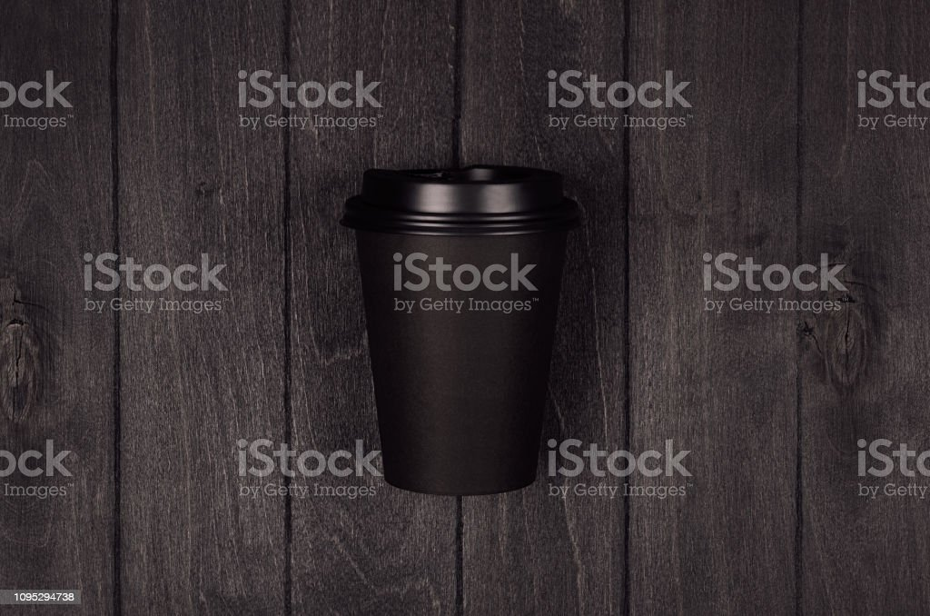 Coffee packing mockup - black paper cup with cap on dark black wood...