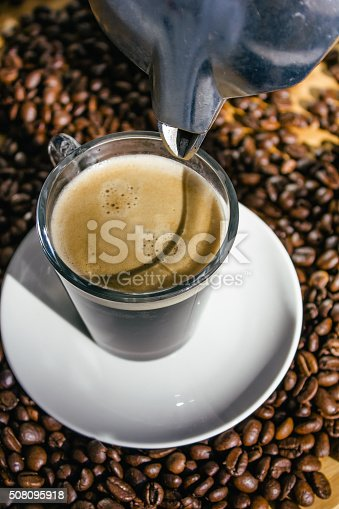 istock Coffee percolator and glass cup of coffee on coffee beans 508095918