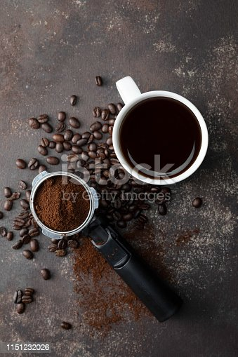 Direct above view of roasted coffee beans and white coffee cup with black coffee on dark brown background.