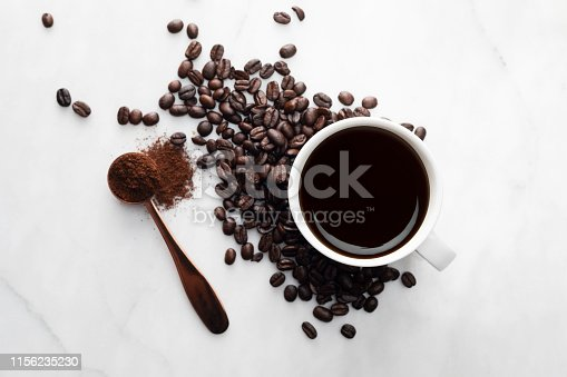Direct above view of roasted coffee beans, white coffee cup with black coffee, one spoon full with blended coffee on white marble background.