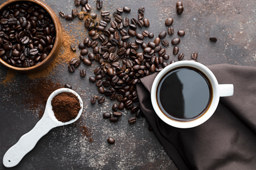 Direct above view of roasted coffee beans, white coffee cup with black coffee, dark brown colored napkin with one white spoon full with blended coffee on dark brown background.