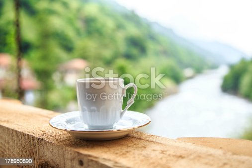 a cup of coffee on table against nature view