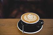Beautiful latte art coffee on wood table in coffee shop