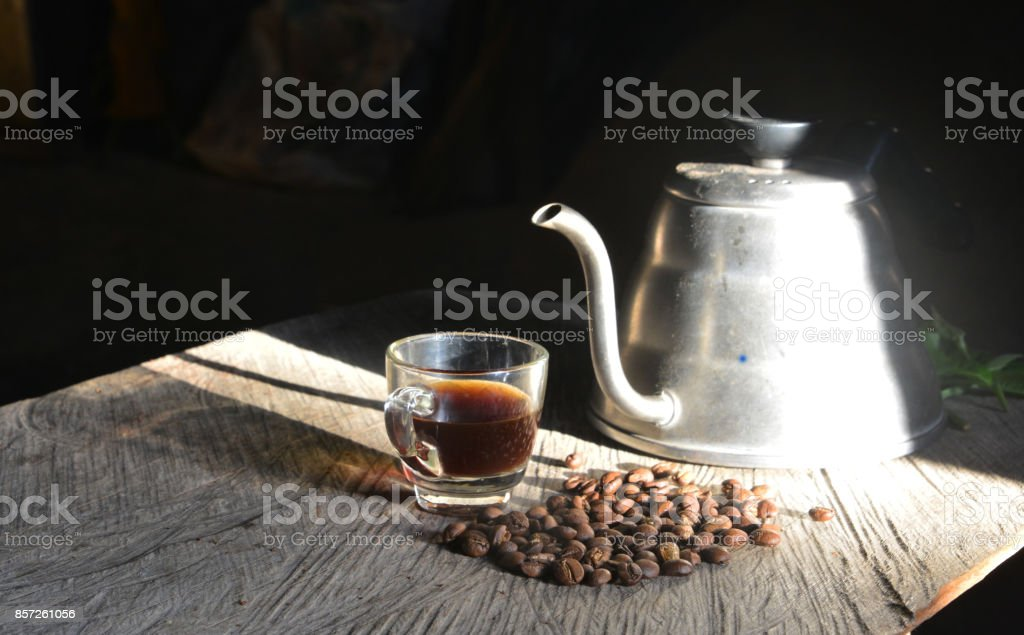 Coffee pot with coffee Cup and coffee bean on a wooden table stock photo