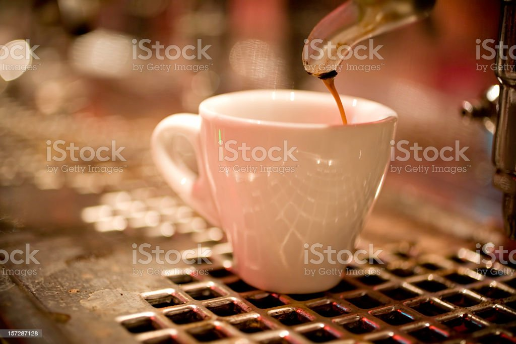 Coffee pouring into a white mug on a steel grate royalty-free stock photo
