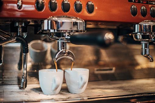 Coffee preparation with espresso machine, no people.