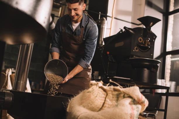 koffie brander gieten koffiebonen in de machine roosteren - geroosterd stockfoto's en -beelden