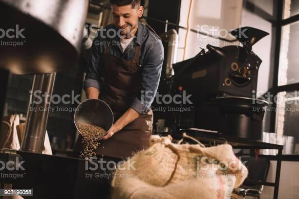 Coffee Roaster Pouring Coffee Beans Into Roasting Machine - Fotografias de stock e mais imagens de Aparelho de Musculação