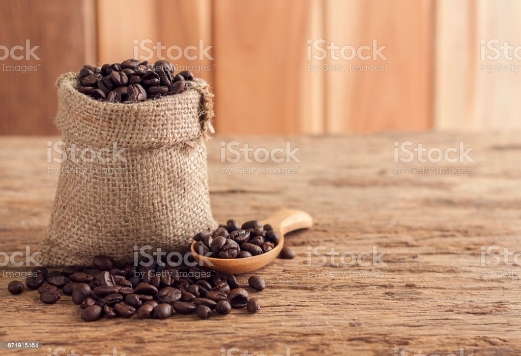Coffee seeds in sack on top wooden table. With space for text you