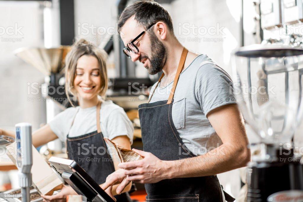 Kaffe säljare arbetar i butiken bildbanksfoto