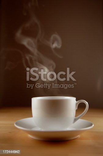 very shallow depth of field image of coffee cup and saucer on wooden table