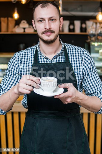 istock coffee shop business owner barista holding cup 955615906