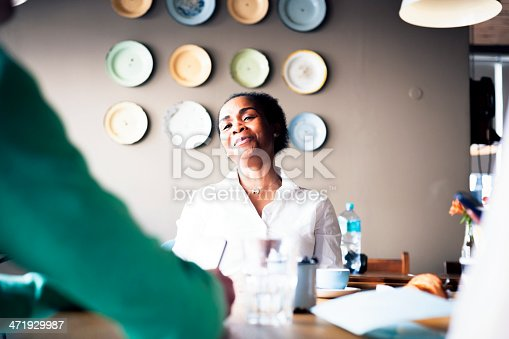 A woman sitting at a wooden table in a coffee shop is amused by something her friend is telling her