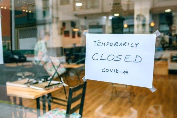 Coffee shop closed by covid-19 Coffee shop closed by covid-19 with workers picking up and cleaning inside closed stock pictures, royalty-free photos & images