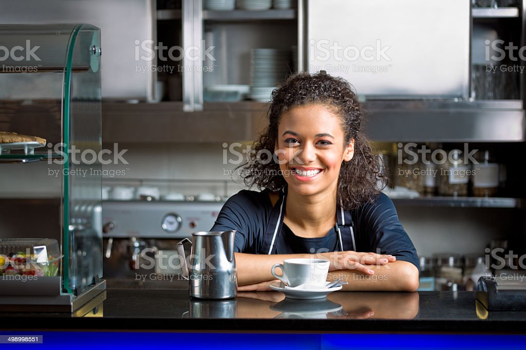 Coffee shop employee Friendly afro american girl standing behind the bar counter and serving coffee in coffee shop, smiling at camera. Adult Stock Photo