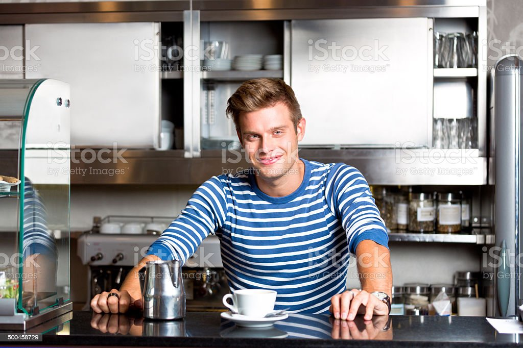 Coffee shop employee Friendly young man standing behind the bar counter and serving coffee in coffee shop, smiling at camera. 20-24 Years Stock Photo