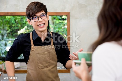 597640822 istock photo Coffee shop entrepreneur young friendly Asian man talkig to customer 1004108468