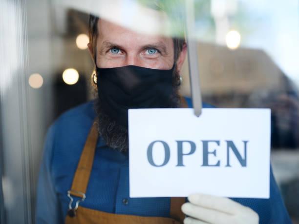 Coffee-Shop-Mann Besitzer mit Gesichtsmaske, geöffnet nach Sperrung Quarantäne. – Foto